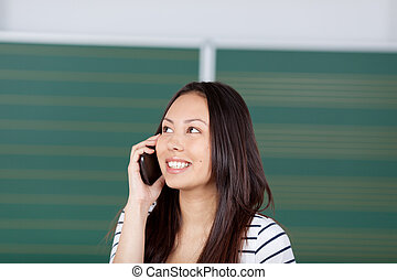 female student using smartphone in classroom