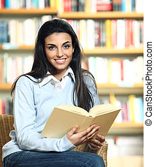 smiling female student with book in hands sitting in a chair in a bookstore - model looking at camera.