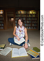 Smiling female student with books on the library floor