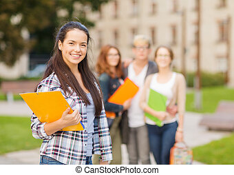 smiling female student with folders