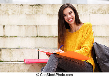 Smiling female student with notebook and pen