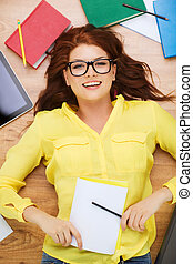 education and home concept - smiling redhead female student in eyeglasses lying on floor with pencil and textbook