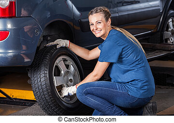 Smiling Female Technician Adjusting Car Tire