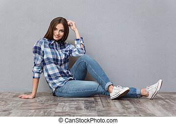 Smiling female teenager sitting on the floor
