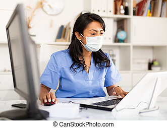 Smiling female therapist working on laptop in medical office