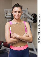 Smiling female trainer with clipboard in gym