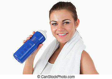 Smiling female with her bottle after workout