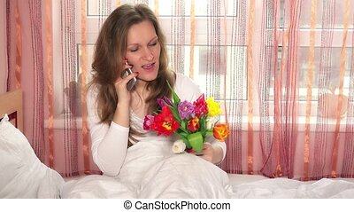 smiling female woman sitting on bed with bouquet of flowers...
