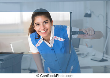 Smiling Female Worker Cleaning Glass Window With Squeegee -...