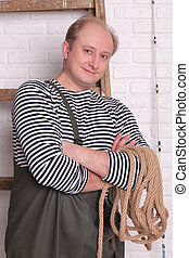 Smiling fisherman in waders with rope