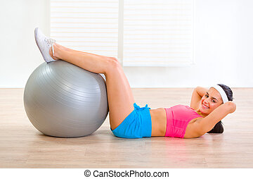 Smiling fit girl doing abdominal crunch on fitness ball at...
