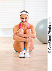 Smiling fit girl in sportswear sitting on floor at home
