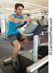 Smiling fit man on the exercise bike