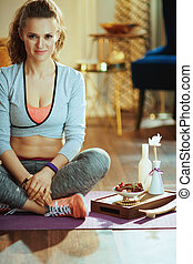 smiling fit sports woman at modern home prepared for meditation