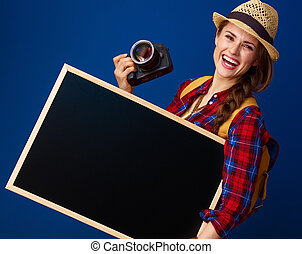 smiling fit tourist woman with DSLR camera showing blank board
