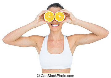 Smiling fit woman holding slices of orange on her eyes