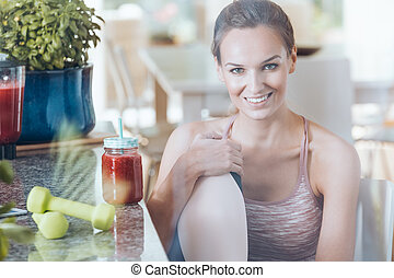 Smiling fit woman in kitchen
