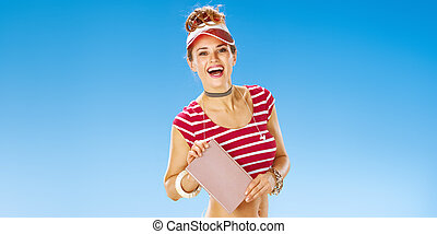 smiling fit woman in red sun visor on beach showing book - ...