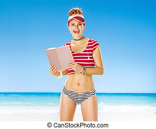 smiling fit woman in red sun visor on beach with book - ...