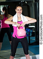 Smiling fit woman lifting kettlebell - Young woman working...
