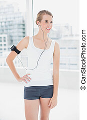 Smiling fit woman listening to music