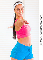 Smiling fit young girl doing exercises at living room