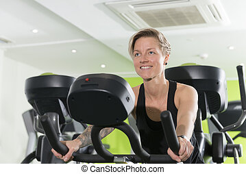 Smiling Fit Young Woman on a Stationary Bike in Gym