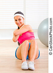 Smiling fitness girl doing abdominal crunch on floor