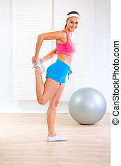 Smiling fitness girl doing stretching exercises at home