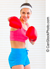 Smiling fitness girl in boxing gloves punching - Smiling...