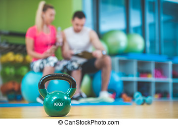 Smiling fitness instructor discussing with man standing in gym