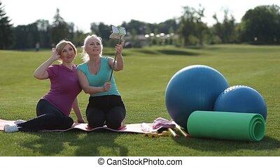 Smiling fitness senior women taking selfie in park -...