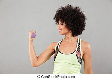Smiling fitness woman doing exercise with dumbbell in studio