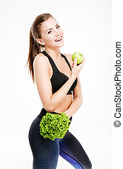 Smiling fitness woman holding apple and lettuce and looking...
