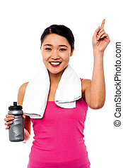 Fitness woman with towel around her neck holding sipper bottle