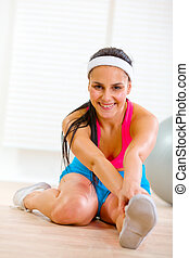 Smiling fitness woman making gymnastics exercise