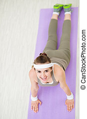 Smiling fitness woman on fitness mat doing yoga