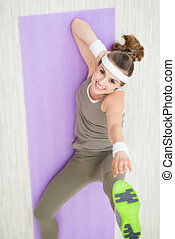 Smiling fitness woman on fitness mat making gymnastics