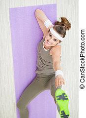 Smiling fitness woman on fitness mat making gymnastics
