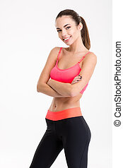 Smiling fitness woman standing with arms folded - Portrait...