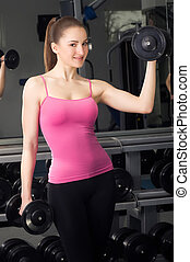Smiling fitness woman with barbells