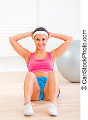 Smiling fitness young girl doing abdominal crunch on floor at living room