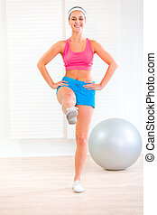 Smiling fitness young girl doing exercises at living room