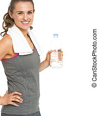 Smiling fitness young woman holding bottle of water