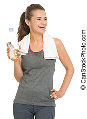 Smiling fitness young woman with bottle of water looking on copy space