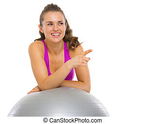 Smiling fitness young woman with fitness ball pointing on copy space