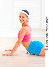 Smiling flexible young female making gymnastics at living room