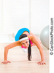 Smiling flexible young girl doing gymnastics exercise at living room