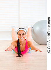 Smiling flexible young girl making gymnastics exercise at living room