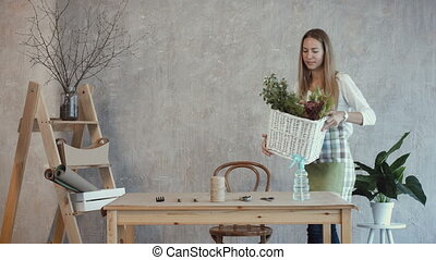 Smiling florist carrying wicker basket with flowers -...
